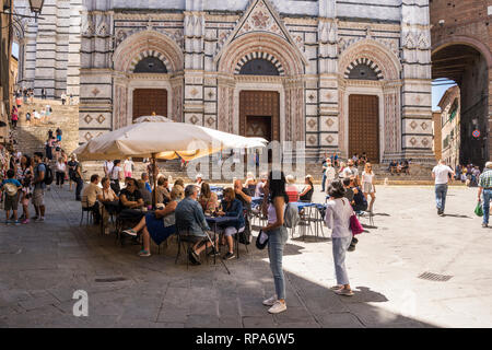 People at pavement cafe close to Duomo di Siena (Siena Cathedral), Tuscany, Italy - Stock Image
