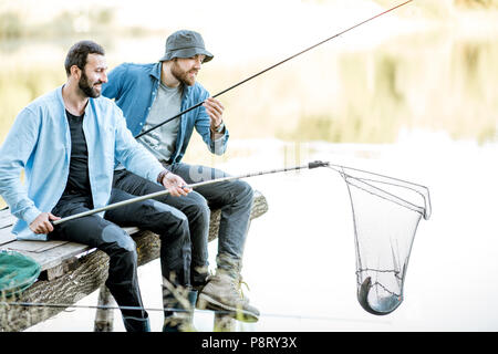 Two friends catching fish with fishing net and rod sitting on the wooden pier at the lake - Stock Image