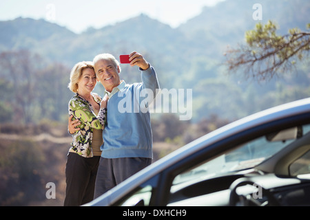 Senior couple taking self-portrait with cell phone outside car - Stock Image