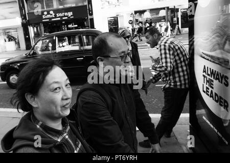 Oriental man and woman rushing down street with woman glancing at the canmera, black cab in the background and 'always the leader' sign in front - Stock Image