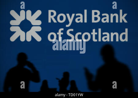 The RBS logo is seen on an LED screen in the background while a silhouetted person uses a smartphone in the foreground (Editorial use only) - Stock Image