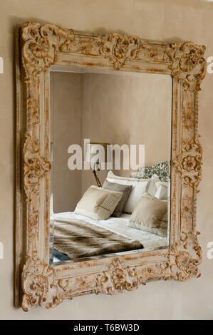 Bed reflected in an old fashioned mirror - Stock Image