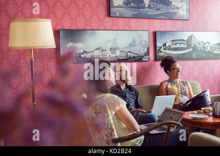 People with laptops sitting by coffee table - Stock Image