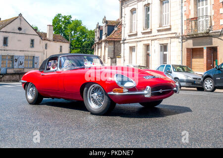 Classic E-type Jaguar driving through French town. - Stock Image