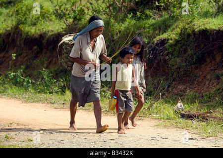A Mangyan woman and two children walk the trail from the Panaytayan community to Mansalay, Oriental Mindoro, Philippines. - Stock Image