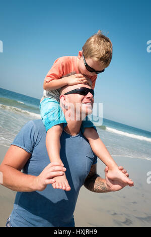 Caucasian father carrying his 4 years old son on his shoulders - Stock Image