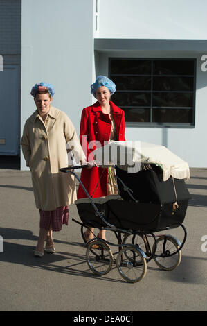 Chichester, West Sussex, UK. 14th Sep, 2013. Goodwood Revival. Goodwood Racing Circuit, West Sussex - Saturday 14th September. Two ladies dressed in period clothing including having their hair in rollers pose with a pram Credit:  MeonStock/Alamy Live News - Stock Image