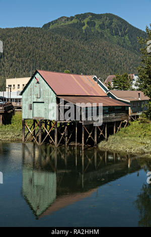 An old wooden stilt boat house on Hammer Slough in Petersburg, Mitkof Island, Alaska. Petersburg settled by Norwegian immigrant Peter Buschmann is known as Little Norway due to the high percentage of people of Scandinavian origin. - Stock Image