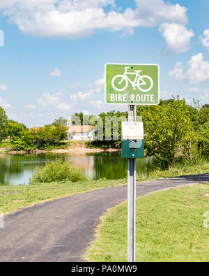 A bike route sign by a path and pond in Sedgwick county park, Wichita, Kansas, USA. - Stock Image