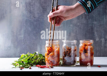Korean traditional fermented appetizer kimchi cabbage and radish salad, fish snack served in glass jars with Vietnamese oregano and chili peppers over - Stock Image