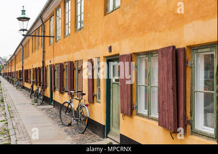 A bicycle for every home: A bicycle is parked in front of each of the houses in a long row house of yellow stucco. - Stock Image