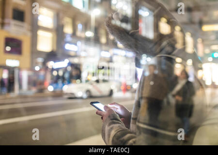 Spain, Madrid, young woman in the city at night next to Gran Via using her smartphone - Stock Image