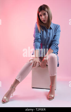 Female in blue jeans shirt and high heels on leg sitting on white cube stool and posing in studio and isolated on pink background. Female fashion - Stock Image