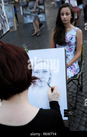 Female artist drawing the portrait of a young dark-haired woman, in Piazza Navona, a popular square among street artists, vendors and performers, Rome - Stock Image