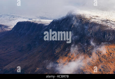 A snow and cloud covered summit of Beinn A Mhuinidh above Loch Maree in the Scottish Highlands, Scotland, UK. - Stock Image