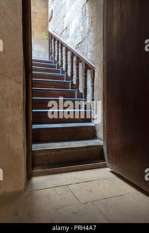 Open wooden door revealing wooden old staircase going up located at the House of Egyptian Architecture historical building, Cairo, Egypt - Stock Image