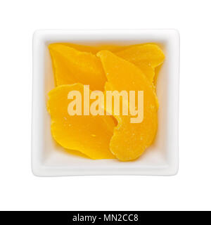 Pieces of candied mango in a square bowl isolated on white background - Stock Image
