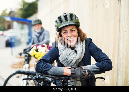 Active senior couple with helmets and electrobikes standing outdoors on a pathway in town. - Stock Image