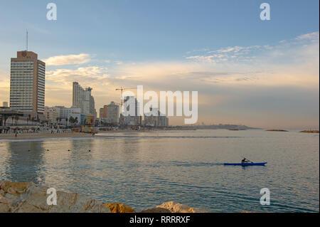 Man in a kayak at dawn, urban beach of Tel Aviv, Israel - Stock Image