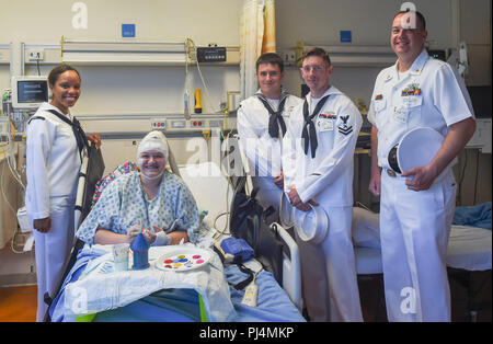 180830-N-OI558-0242 (Aug. 30, 2018) Sailors assigned to the Arleigh Burke-class guided-missile destroyer USS Dewey (DDG 105) and the Avenger-class mine countermeasures ship USS Scout (MCM 8) pose with a patient at the Children's Hospital of Orange County during Los Angeles Fleet Week (LAFW).  LAFW is an opportunity for the American public to meet their Navy, Marine Corps and Coast Guard teams and experience America's sea services. During fleet week, service members participate in various community service events, showcase capabilities and equipment to the community, and enjoy the hospitality o - Stock Image