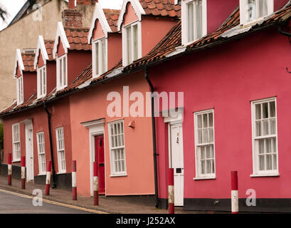 Row of Terraced Cottages painted various shades of Pink, with Red and White Bollards in front, Bungay, Suffolk, - Stock Image
