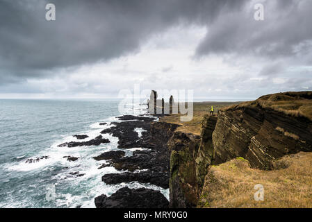 Snaefellsnes Peninsula, Western Iceland, Iceland. Londrangar sea stack and coastal cliffs. A man is standing on the cliff - Stock Image