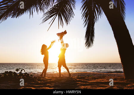 Happy family having fun under palm on sunset beach - Stock Image