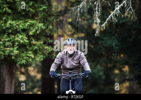 An active senior man with helmet and electrobike cycling outdoors on a road in nature. - Stock Image