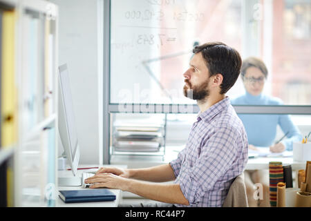 Serious manager or designer looking at computer screen while entering data or searching for websites in the net - Stock Image