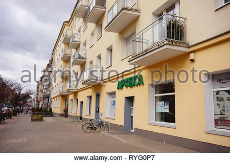 Poznan, Poland - March 8, 2019: Pharmacy store with parked bicycle in a apartment building by a sidewalk on the Slowackiego street. - Stock Image