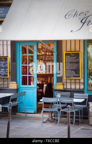 Man seated near the doorway of Chez Julien - a Cafe in the 4th Arrondissemont, Paris France - Stock Image