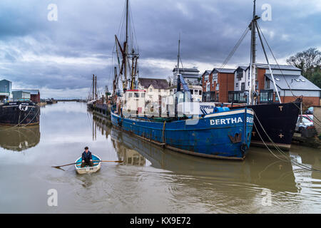 A man rowing a small boat past MV 'Bertha' and other ships at Anchorage Hill, Maldon, Essex, England, UK - Stock Image