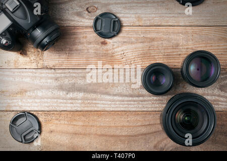 Camera lenses and a dslr digital camera on a wooden table, top view - Stock Image