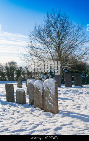 The village churchyard at Bitchfield, Grantham, Lincolnshire in the snow - Stock Image