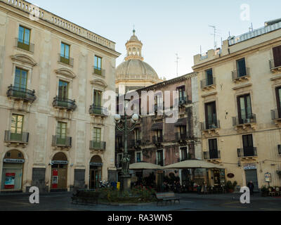 Bronze lamp post in Piazza Universita, Catania, Island of Sicily, Italy. The dome is that of the Church of the Badia di Sant'Agata. - Stock Image