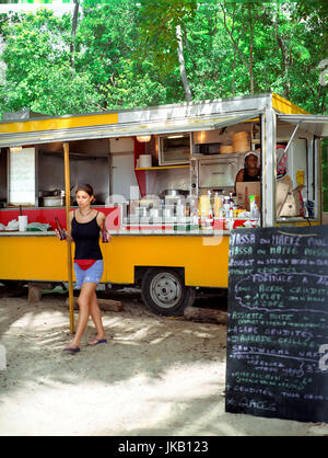 An attractive female tourist buys some beers from an beach side food stall. Point de Salines (Plage des Salines) - Stock Image
