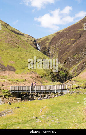 Two walkers cross the footbridge over the Tail Burn beneath The Grey Mare's Tail waterfall, near Moffat, Dumfries & Galloway, Scotland, UK - Stock Image