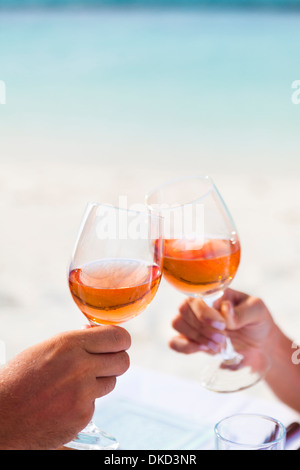 A couple touch wine glasses in the Maldives - Stock Image