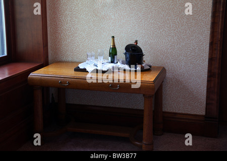Champagne bottle, glasses and ice bucket on a table in a hotel hallway - Stock Image