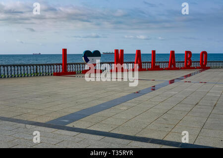Letters reading 'I love Malabo' in red on a walkway in front of the sea in Malabo, the capital of Equatorial Guinea, which is on Bioko island. - Stock Image