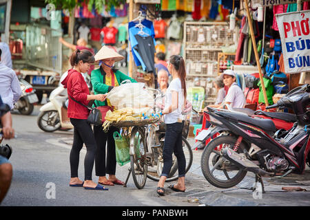 A street seller wearing traditional conical straw hat helping customers. This is a common sight in Hanoi's Old Quarter district. - Stock Image