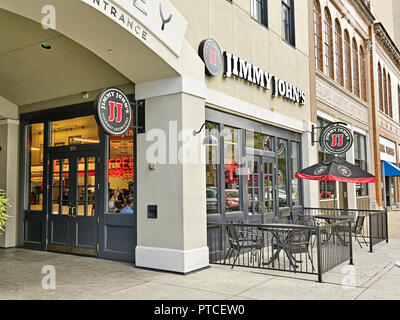 Jimmy John's fast food sandwich shop or restaurant front exterior entrance with small patio in downtown Montgomery Alabama, USA. - Stock Image