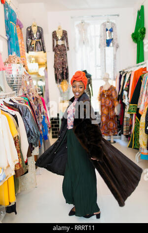 Portrait confident, stylish young woman trying on fur coat in clothing store - Stock Image