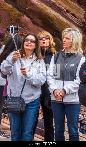 Three woman use a selfie stick to take their group photo with cell phone at Red Rocks Park Amphitheater near Morrison Colorado US. Photo taken in May. - Stock Image