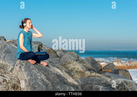 woman listening to music with headphones and ipad, sitting on rocks by the sea - Stock Image