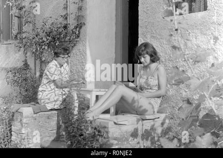 two women sitting in their front garden reading books 1960s hungary - Stock Image
