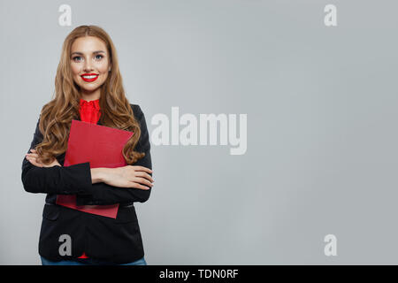 Happy business woman standing against white wall background. Businesswoman in black suit portrait - Stock Image