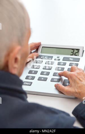 Very old and visually impaired woman sitting at a table using a desktop calculator with an extra large keypad - Stock Image