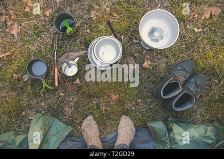 camping gear and traveler feet by the tent. top view - Stock Image