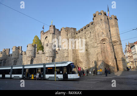 A modern city tram in front of the medieval castle of Gravensteen in the heart of the Belgian city of Ghent - Stock Image